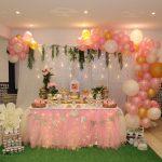 Una mesa dulce y una estructura de globos rosa y dorado para la comunión de Teresa